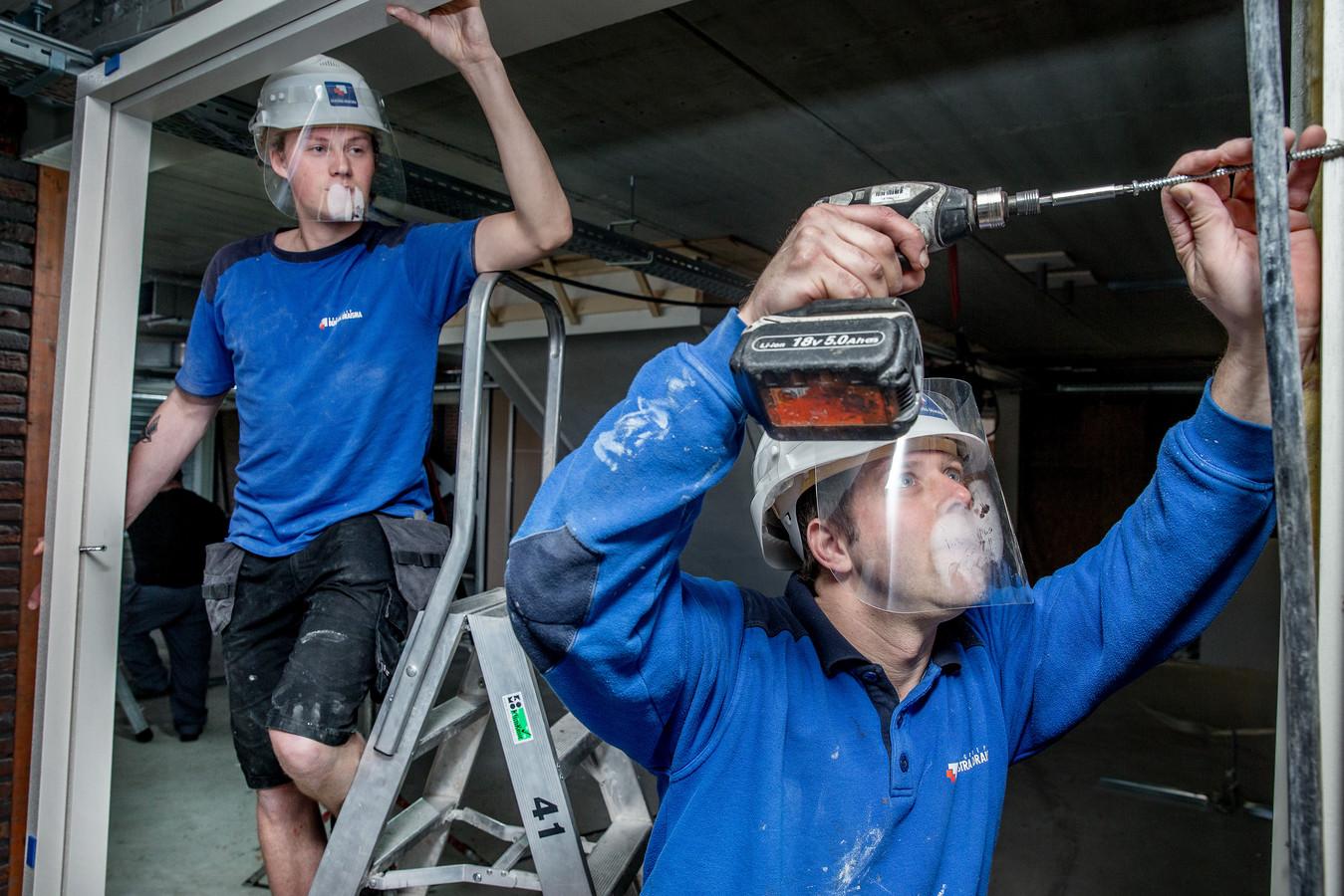 De bouwvakkers van bouwbedrijf Dijkstra Draisma dragen op hun werkplek in Hoorn de door het bedrijf zelf ontwikkelde veiligheidsmaskers als ze werkzaamheden moeten uitvoeren waarbij de 1,5 meter afstand niet kan worden aangehouden.