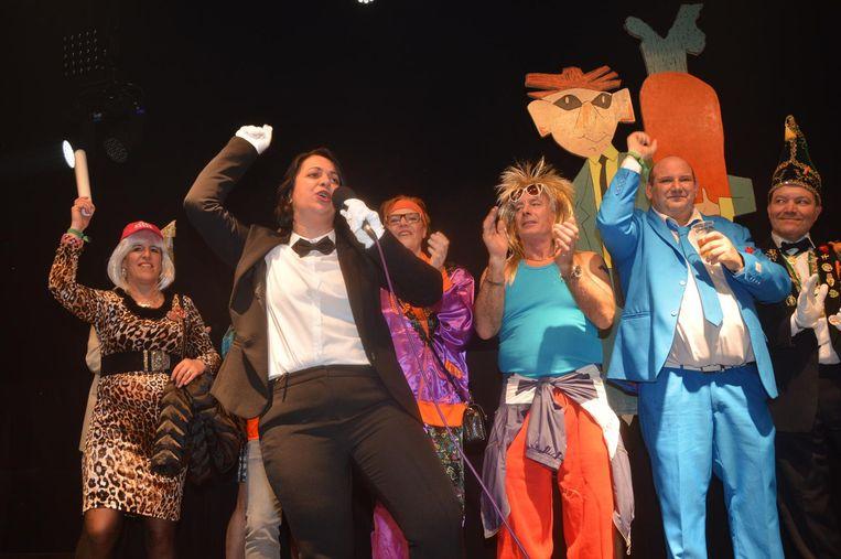 Voor de kroning brengt Prins Chena haar carnavalsliedje. Op de achtergrond burgemeester Tania De Jonge (in paars) en enkele schepenen ook in thema 'camping Cosmos' gekleed.