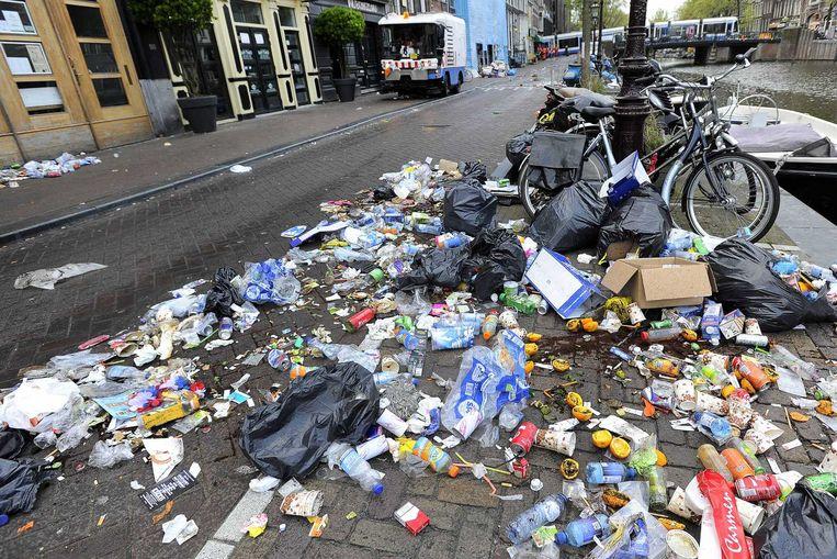 Schoonmaakploegen in het centrum ruimen de rommel op die achtergebleven is na de viering van Koningsdag in de hoofdstad Beeld anp