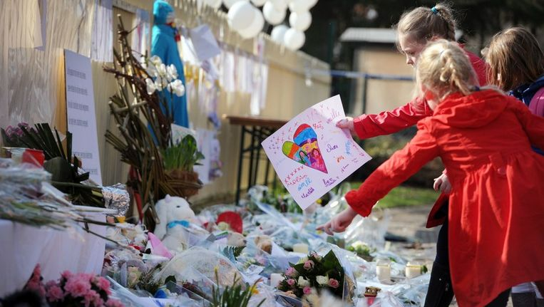 Kinderen leggen tekeningen neer ter gedachtenis aan hun omgekomen leeftijdgenootjes. Beeld null