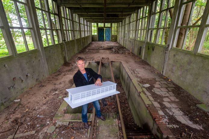 Gerrit van Middelkoop in de remise met een maquette die hij heeft gemaakt van het gebouwtje. In de vloer ligt een smeerput.