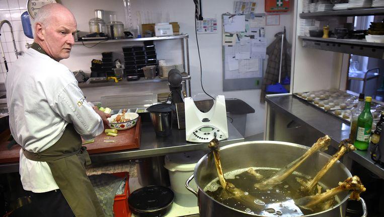 Arjan Smit in de keuken van zijn restaurant De Pronckheer in Cothen. In de pan: een doodgereden ree. Beeld Marcel van den Bergh / de Volkskrant