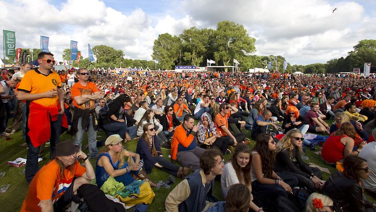 In oranje geklede bezoekers van Parkpop kijken naar de WK-wedstrijd tussen Nederland en Mexico op een groot scherm worden getoond. Beeld anp