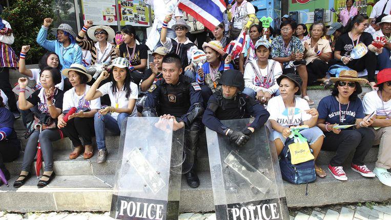 Twee politieagenten in Bangkok zitten vrijdag temidden van de demonstraten. Beeld ap