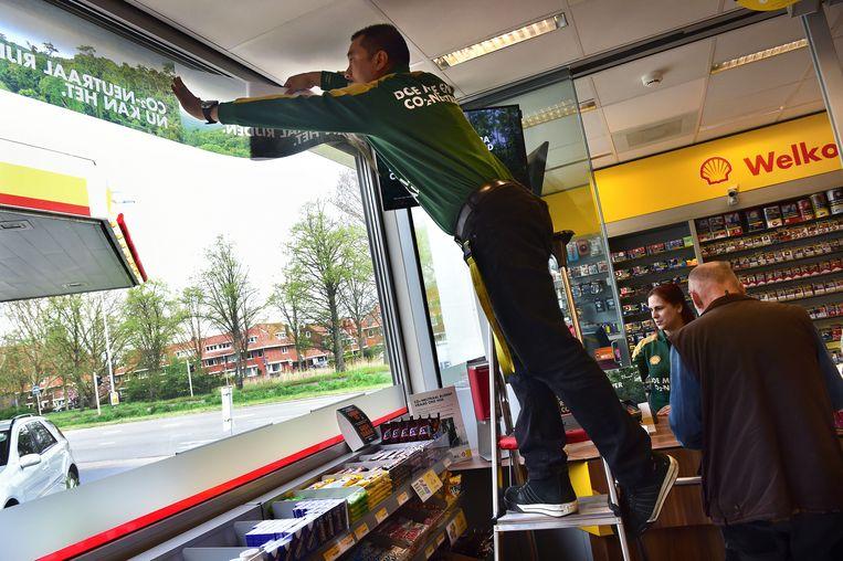 Een pomphouder plakt de aankondiging van CO2-neutraal rijden voor het raam. Beeld Marcel van den Bergh