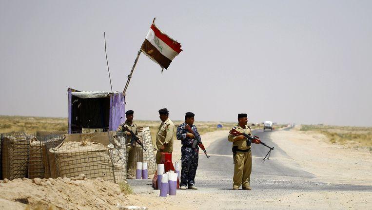 Irakese soldaten bewaken een weg in hun strijd tegen IS. Beeld afp