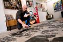 Nick Twaalfhoven werkt met de spuitbus Johnny Cash bij op de vloer van zijn winkel.