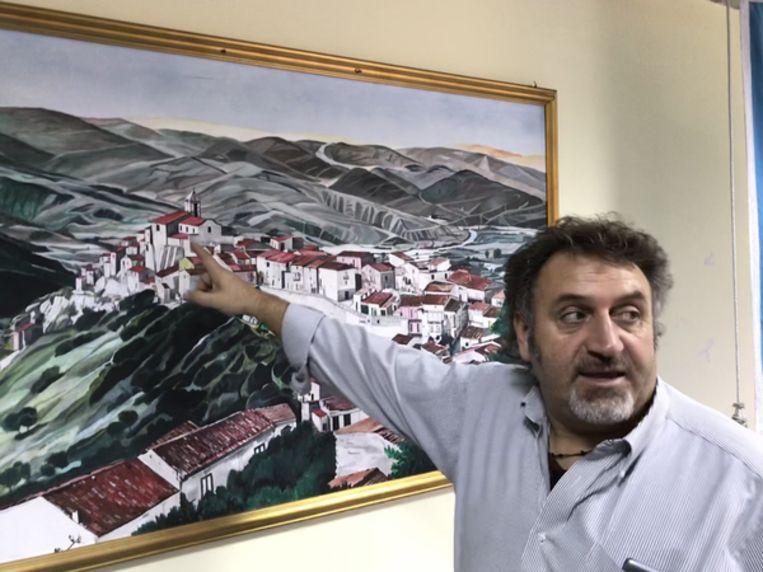 Burgemeester Enrico Fratangelo voor een  schilderij van het dorp.    Beeld