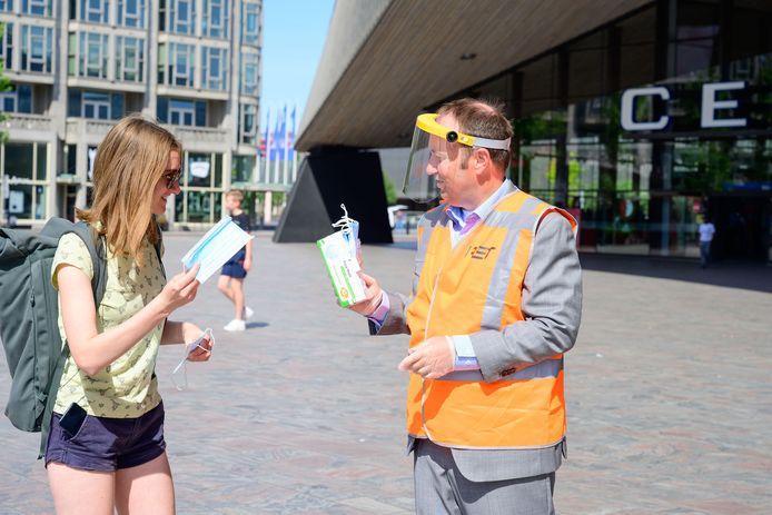 Een vrouw ontvangt een mondkapje van Maurice Unck, de directeur van de RET. Het gelaatsscherm dat Unck op zijn hoofd heeft, behoort nu tot de vaste uitrusting van de conducteurs in de voertuigen van het Rotterdamse vervoersbedrijf.
