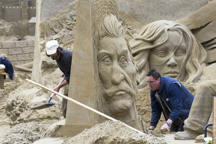 Zandkunstenaars boetseren hun werk voor het Zandsculpturenfestival van 2015.