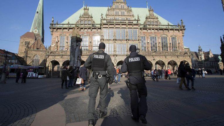Gewapende politiemannen patrouilleren door het centrum van Bremen. Beeld null
