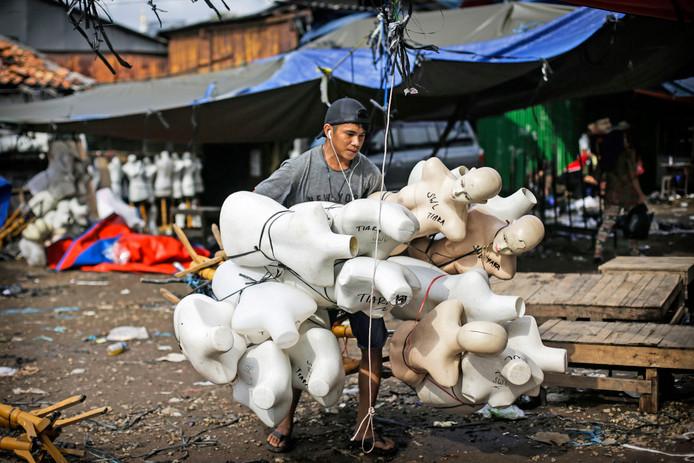 Een Indonesische marktkoopman, draagt een tros etalagepoppen naar zijn auto. Foto Mast Irham