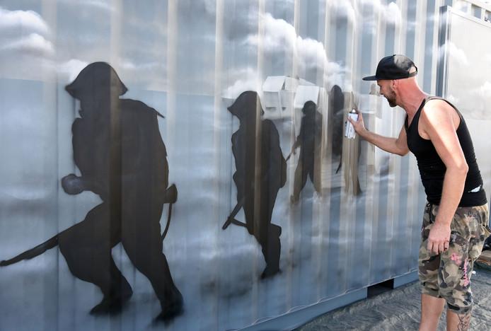 Martijn Prins schildert de landing bij Vlissingen op een container.