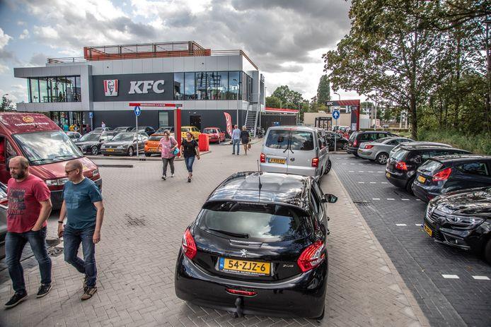 Drukte op de parkeerplaats van het foodcourt. Door de lange rij bij KFC komt het op de parkeerplaats geregeld vast te staan.