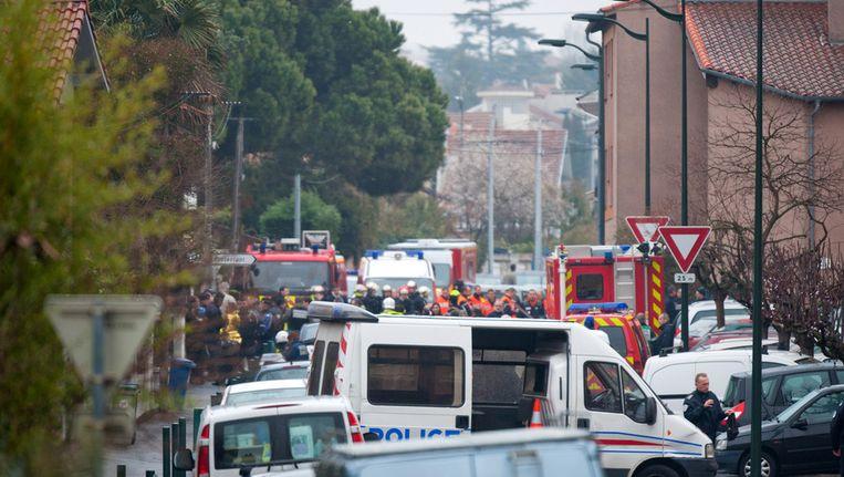 Politie en brandweer in de wijk van het belegerde pand. Beeld getty