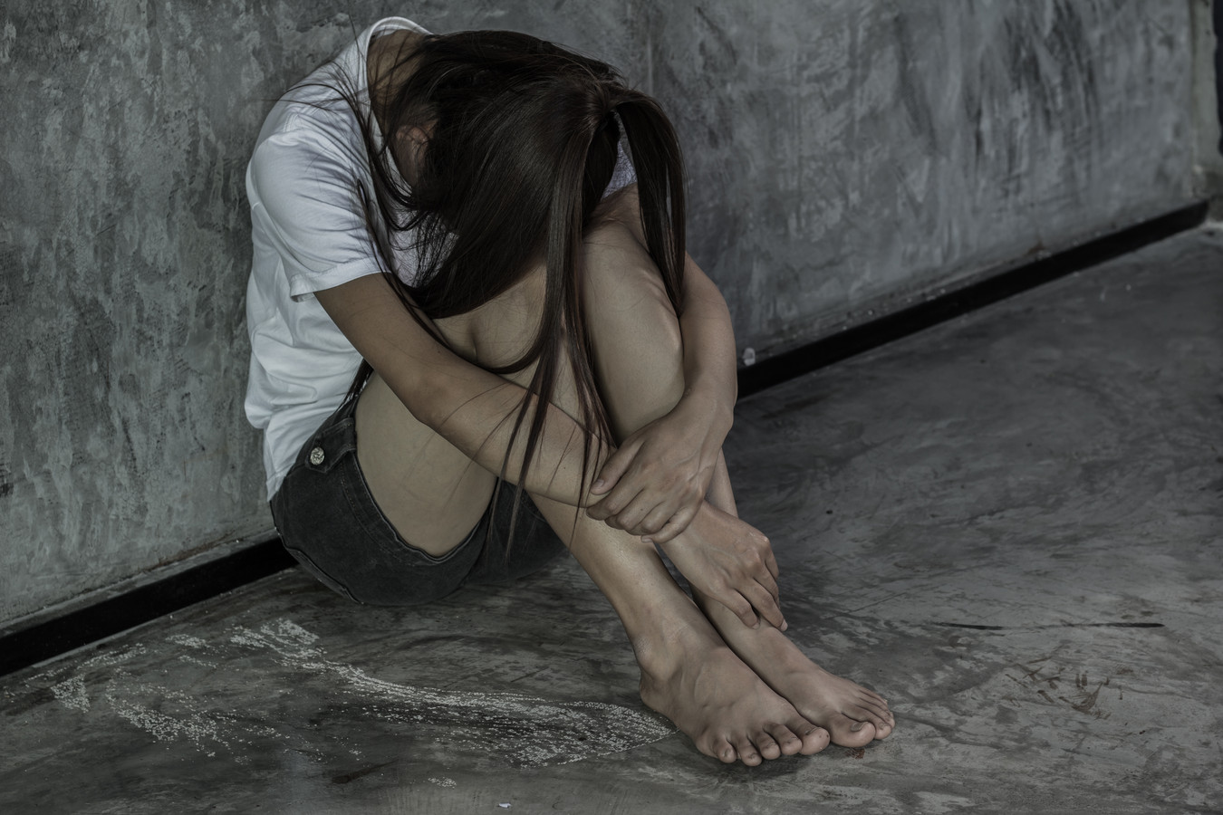 Stockfoto mensenhandel. A girl with sadness sits hugging, stopping violence against women, International Women's Day