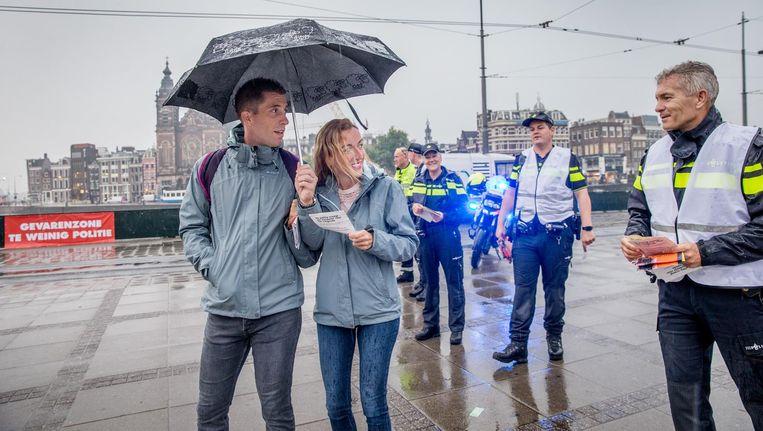 Actievoerende politieagenten delen flyers uit bij het Centraal Station in Amsterdam. Beeld Jean-Pierre Jans