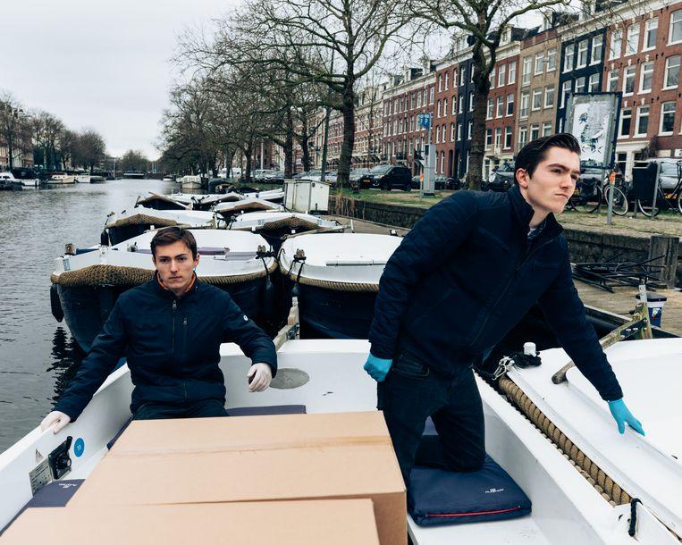Twee bezorgers van Sloepdelen met de pakketten op weg naar de klanten. Beeld Rebecca Fertinel