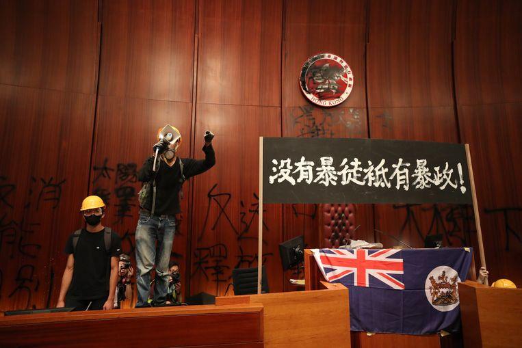 Demonstranten maandag in het parlementsgebouw van Hongkong, met op de muur door hen gespoten leuzen. Beeld EPA