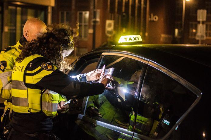 Politieagent controleren een taxi in Enschede