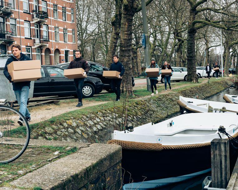 Medewerkers van botenverhuurbedrijf Sloepdelen Amsterdam dragen de pakketten naar de boten voor verdere bezorging.  Beeld Rebecca Fertinel