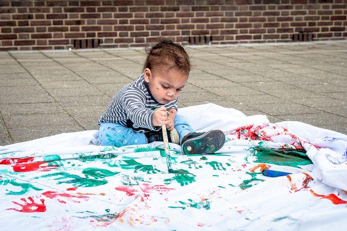 Kinderen maken spandoeken voor de drone, de anderhalf jaar oude Djilson is er maar druk mee bij kinderopvang KindeRdam in Vreewijk.