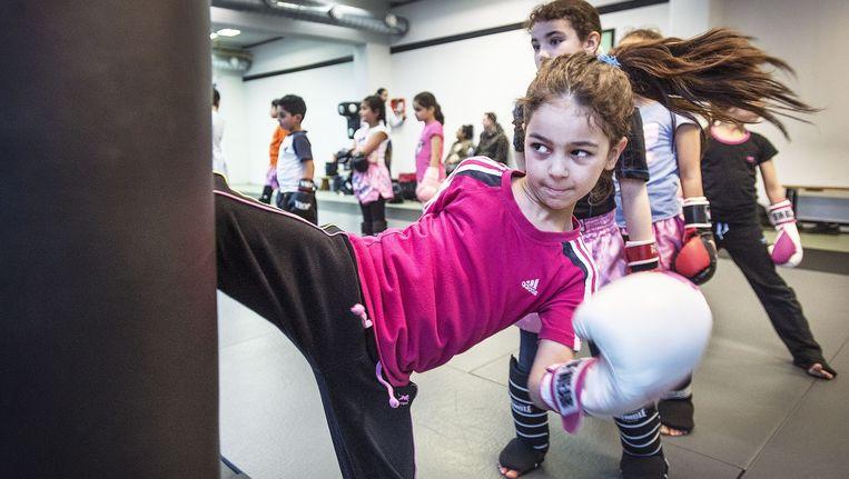 Thai-boksles voor jonge kinderen op de school van Khalid Chennouf in het Oude Westen van Rotterdam. Vooral de meisjes zijn bloed serieus. Beeld Guus Dubbelman / de Volkskrant