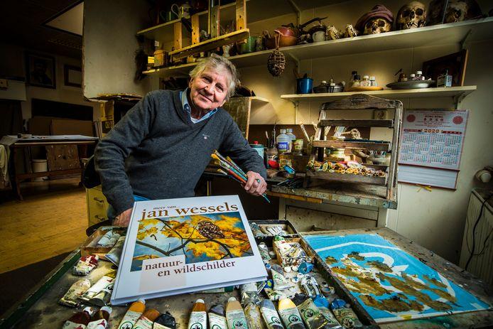 Jan Wessels, natuur-en wildschilder, in zijn atelier met voor hem zijn nieuwe boek.