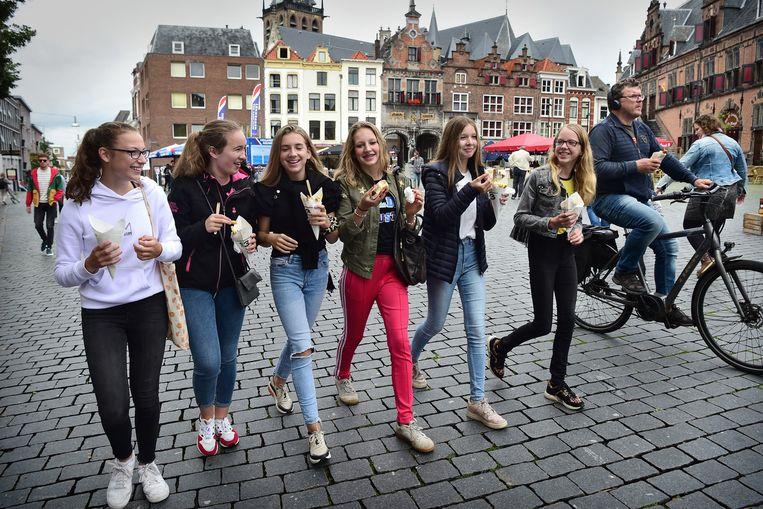Vriendinnen lopen over de Grote Markt in Nijmegen. Beeld Marcel van den Bergh