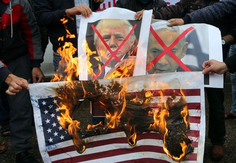 Palestijnen verbranden posters van de Israelische premier Netanyahu en de Amerikaanse president Donald Trump.  Beeld REUTERS