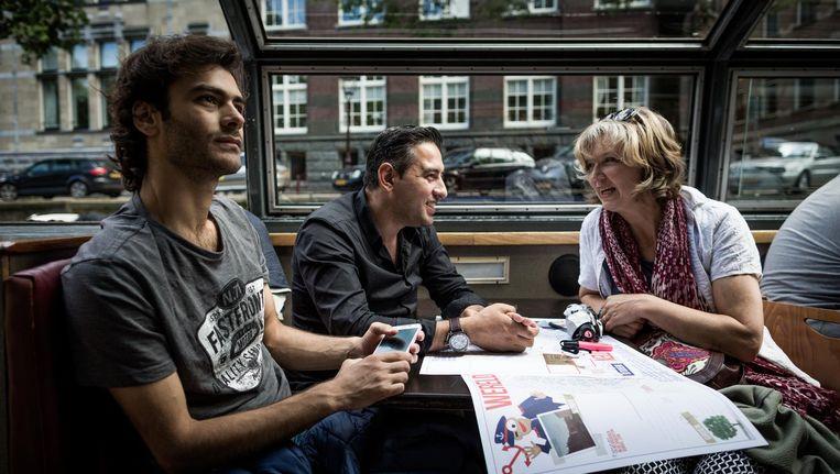 Vluchtelingen bekijken de grachten van Amsterdam tijdens een rondvaart aangeboden door Museum Amsterdam. Beeld anp