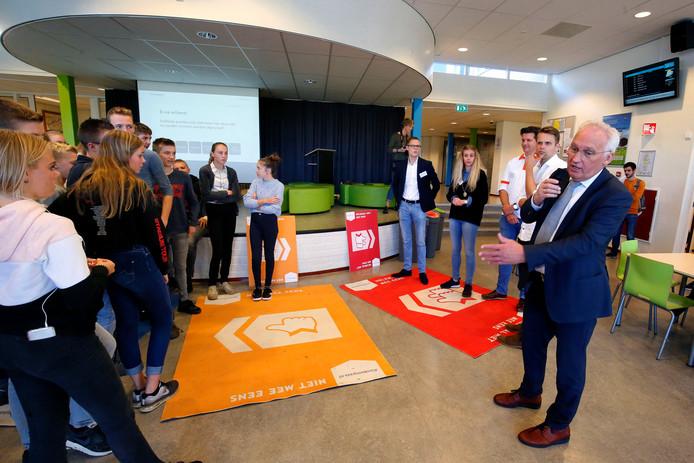 Burgemeester Dirk van den Borg leidt het debat tussen scholieren en lokale politici in de aula van het Wellantcollege.