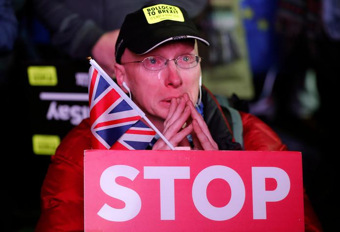 Een tegenstander van de brexit huilt op de stoep voor het parlementsgebouw nadat de deal van May is weggestemd.