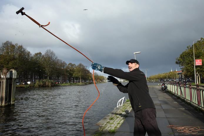 Op deze foto uit 2017 demonstreert een magneetvisser uit Rotterdam hoe magneetvissen in zijn werk gaat. Het is vissen met een zeer sterke magneet in de hoop iets waardevols naar boven te hengelen. Er schijnen magneten te zijn waar je 100 kilo of meer mee naar boven kunt trekken.