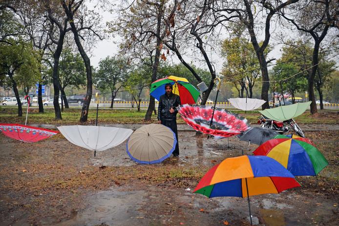 Een Pakistaanse parapluverkoper wacht op een regenachtige ochtend in Islamabad op klanten . Foto Aamir Qureshi