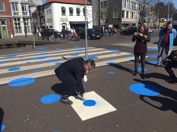 Wethouder Alfred Arbouw brengt in april 2018 een blauwe stip aan op de Markendaalseweg op de plaats waar de Nieuwe Mark straks gaat lopen.
