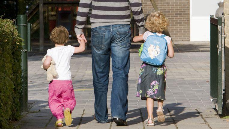 Een vader brengt zijn kinderen naar school. Beeld anp