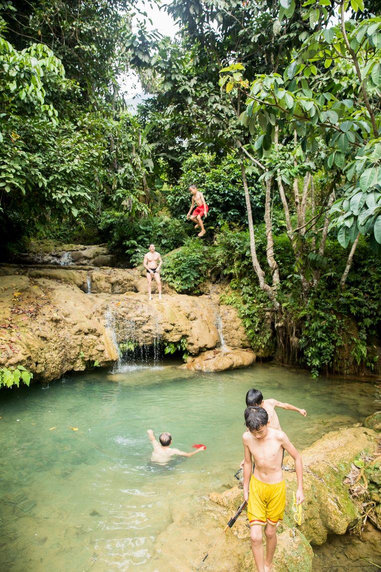 Spelende kinderen samen met Noël van Bemmel bij een waterval in het Pu Loung gebied. Beeld Marie Wanders