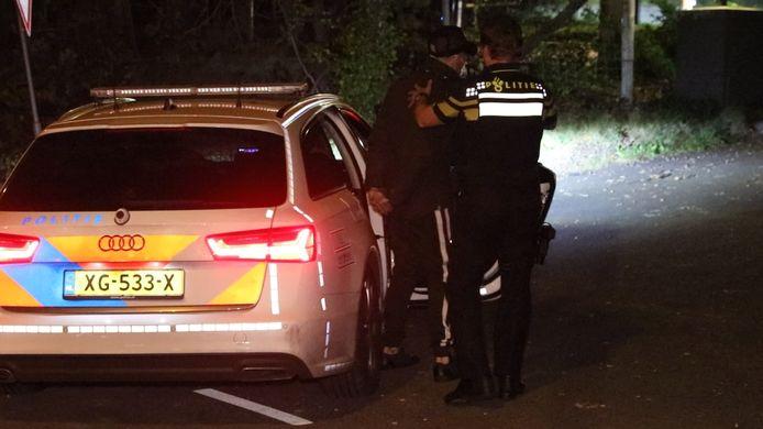 Een van de drie mannen wordt in een politiewagen gezet na de aanhouding in Arnhem.