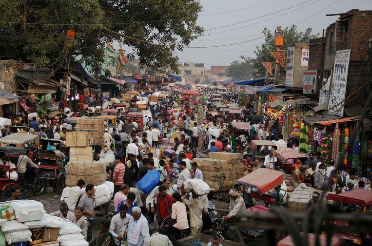 Een mensenmenigte op een markt in New Delhi. India is na China het land met de meeste inwoners.   Beeld AP
