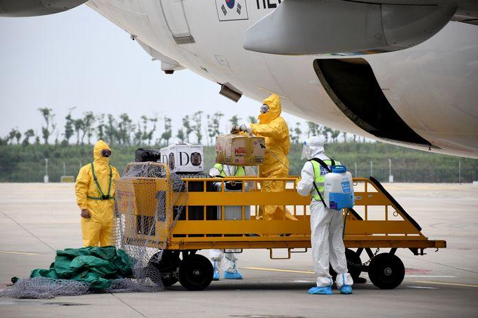 Personeel in beschermende pakken desinfecteert de bagage die uit het vliegtuig komt.