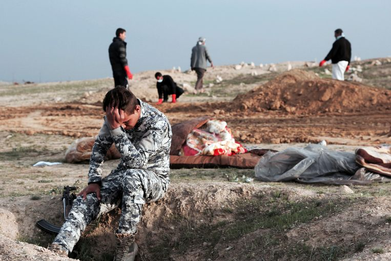 Een Iraakse politieman moet (in maart 2017) even tot zichzelf komen, te midden van lichamen die gevonden zijn in een massagraf bij de stad Mosul. Foto AP / Christian Stephen Beeld AP