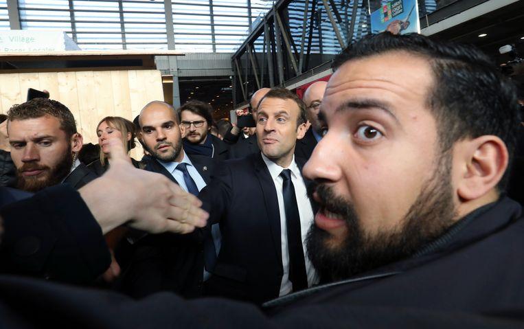 De Franse president Macron schudt handen, terwijl zijn veiligheidschef Benalla (rechts) een oogje in het zeil houdt.  Beeld EPA