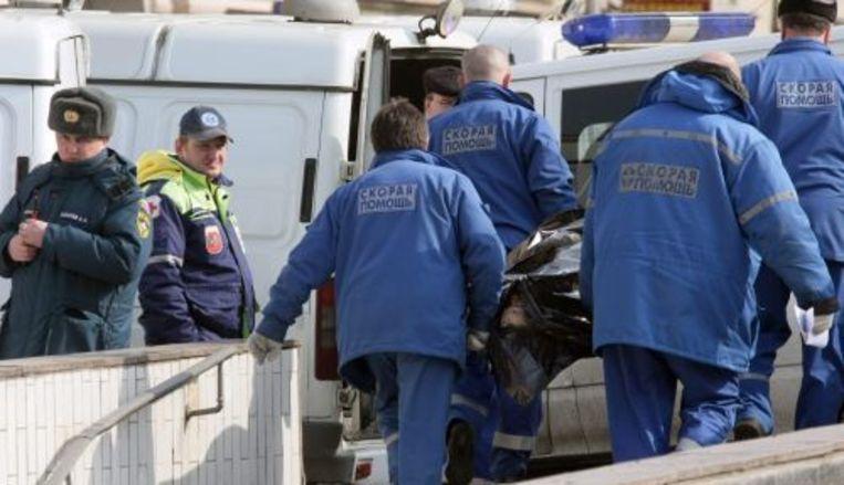 Ambulancepersoneel brengen lichamen naar buiten. ANP Beeld