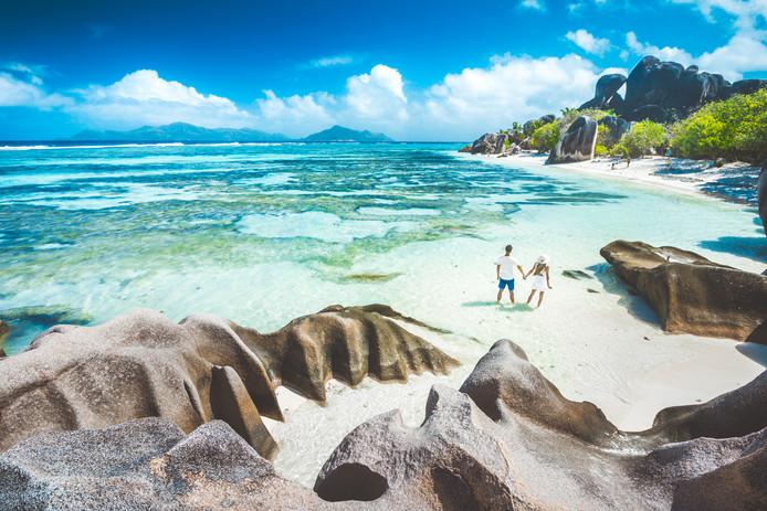 La Digue, Seychellen Een strand met wuivende palmbomen.