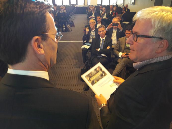 René Peerenboom (links), wethouder van Uden, overhandigt de Omgevingskoers Noordoost-Brabant aan gedeputeerde Erik van Merrienboer.
