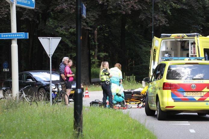 De gewonde wielrenner wordt behandeld door het ambulancepersoneel.