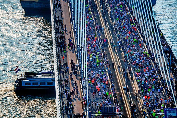 Lopers rennen over de Erasmusbrug na de start van de 39ste editie van de marathon van Rotterdam.