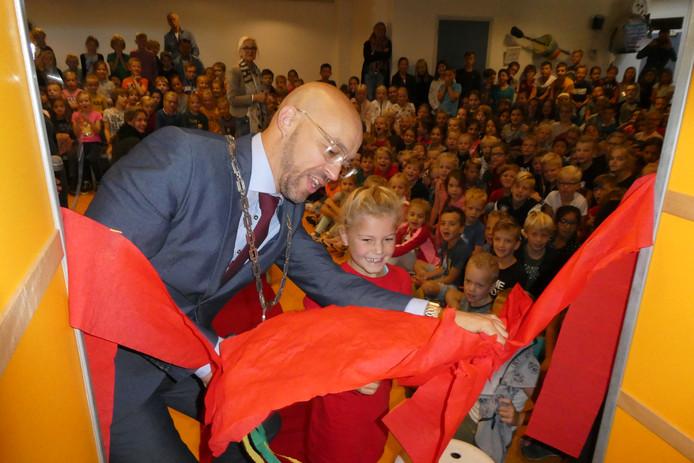 Leerlinge Lynn (6) en burgemeester Han Looijen openen samen de nieuwe schoolbibliotheek in De Bolster. Ze knippen een rode strik aan flarden.