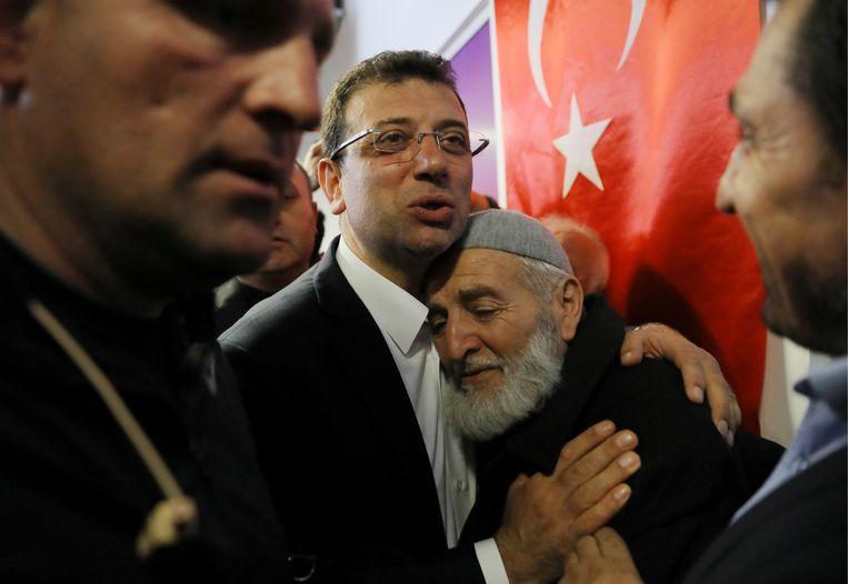 Ekrem Imamoglu, burgemeesterskandidaat van de oppositiepartij CHP, omarmt een van zijn supporters, in Istanbul. Beeld REUTERS